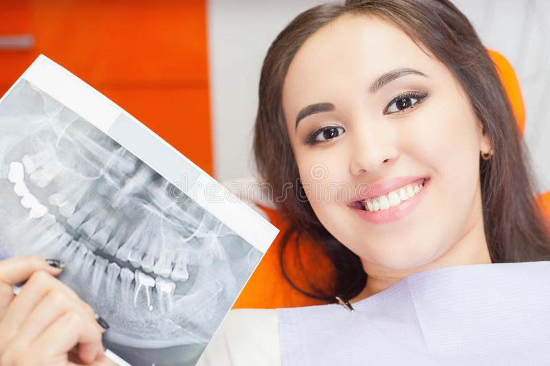 Patient beautiful girl holding x-ray picture of her teeth stock photography