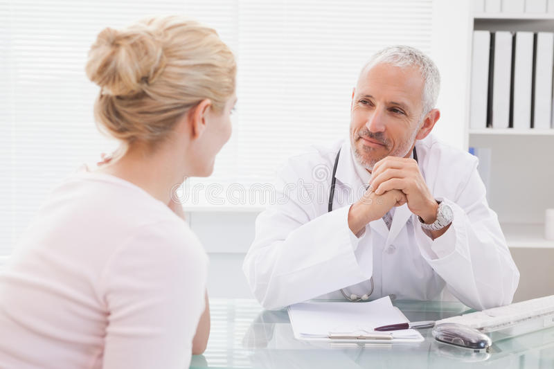 Patient consulting a happy doctor royalty free stock photos