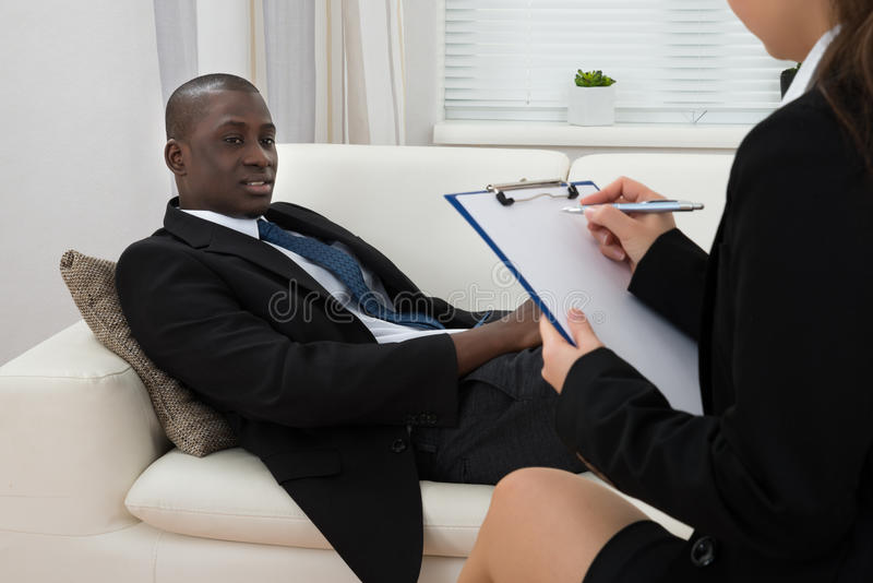 Patient On Couch And Psychiatrist Writing On Clipboard royalty free stock image
