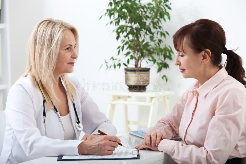 Patient dans le bureau du ` s de docteur, elle reçoit une médecine de prescription photos libres de droits