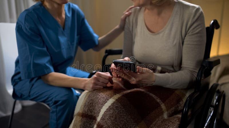 Patient de aide de clinique de fauteuil roulant d'infirmière féminine pour utiliser le smartphone, appui images stock
