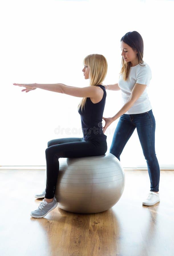 Patient de aide de physiothérapeute pour faire l'exercice sur la boule de forme physique dans la physio- chambre photo libre de droits