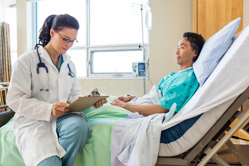 Patient de docteur Holding Clipboard While regardant photos libres de droits