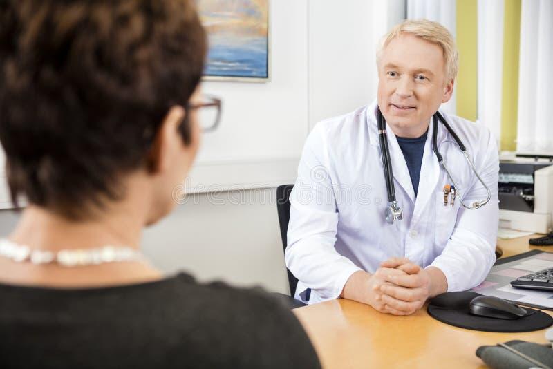 Patient de docteur Looking At Female au bureau photo stock