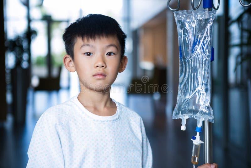 Patient de garçon tenant le support intraveineux d'égouttement d'iv dans le couloir images stock
