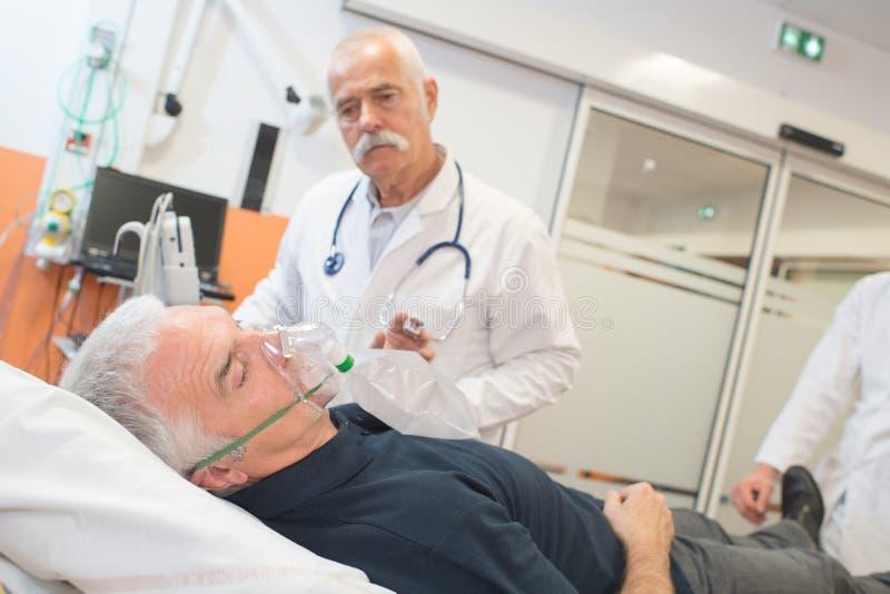 Patient de vieil homme se trouvant sur le lit d'hôpital avec le masque à oxygène photographie stock