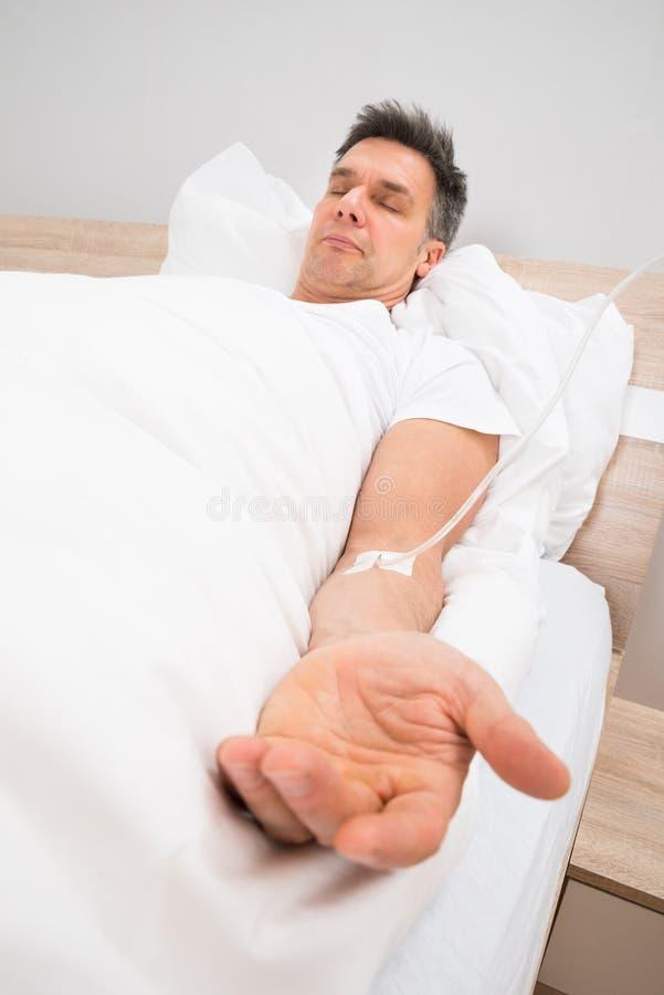 Patient, der auf Bett mit iv-Tropfenfänger stillsteht stockfotografie