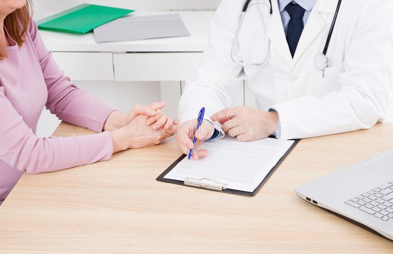 Patient, der bedacht auf einen männlichen Doktor erklärt geduldige Symptome oder stellt eine Frage hört, wie sie Schreibarbeit zu stockfoto