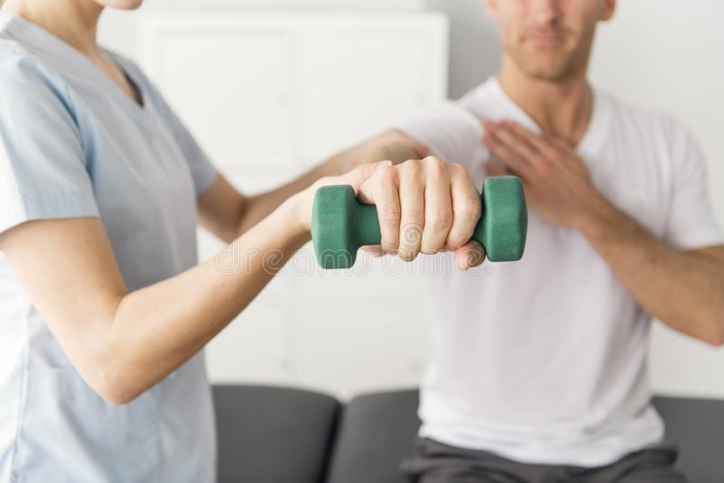 Patient an der Physiotherapie, die körperliche Bewegungen mit seinem Therapeuten tut lizenzfreies stockbild