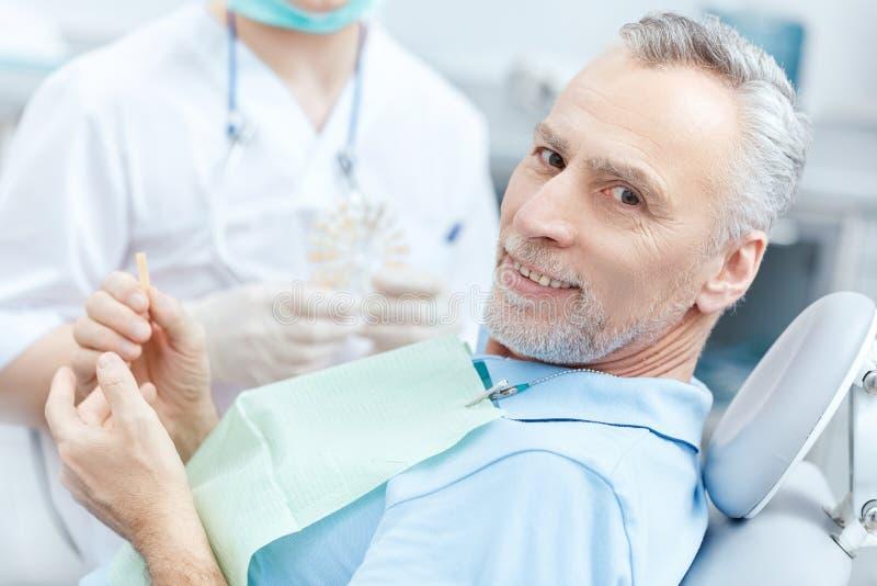 Patient, der Zahnprobe beim Besuchen des Zahnarztes betrachtet lizenzfreies stockbild