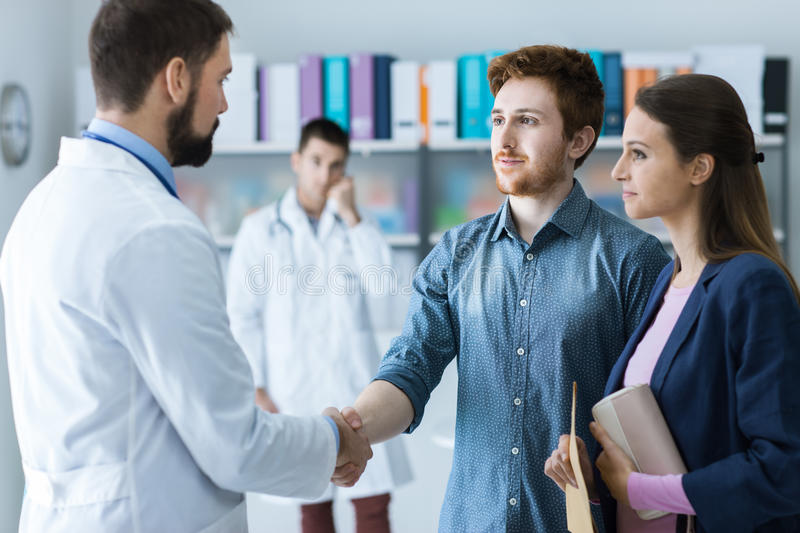 Patient and doctor shaking hands stock photos