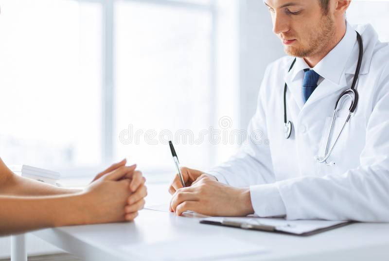Patient And Doctor Taking Notes Royalty Free Stock Photography