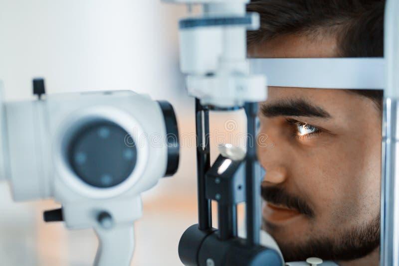 Patient eller kund på den skurna upp lampan på optometrikern eller optiker fotografering för bildbyråer