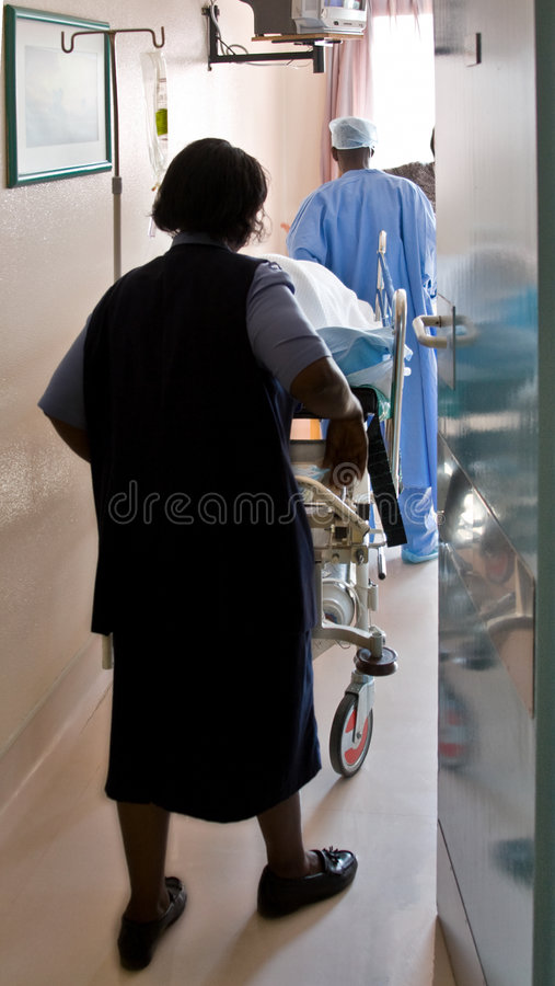 Patient emergency. Healthcare personnel carry one patient after surgery in the recovery room royalty free stock photo