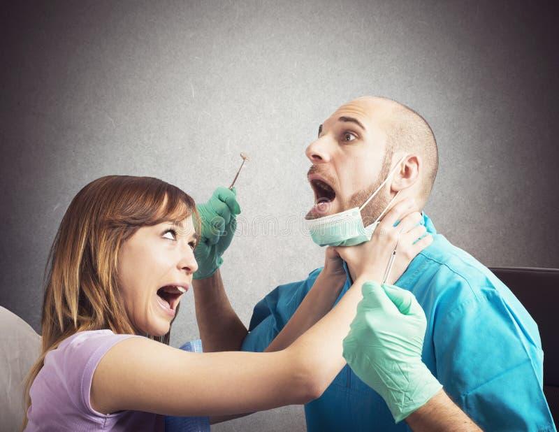 Patient fâché par le dentiste image stock