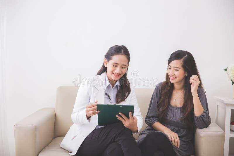 Patient féminin asiatique consultant un docteur féminin images libres de droits