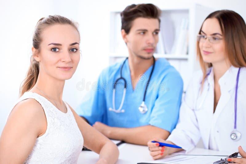 Patient féminin blond heureux à côté de quelques médecins dans l'hôpital se reposant à la table photo libre de droits