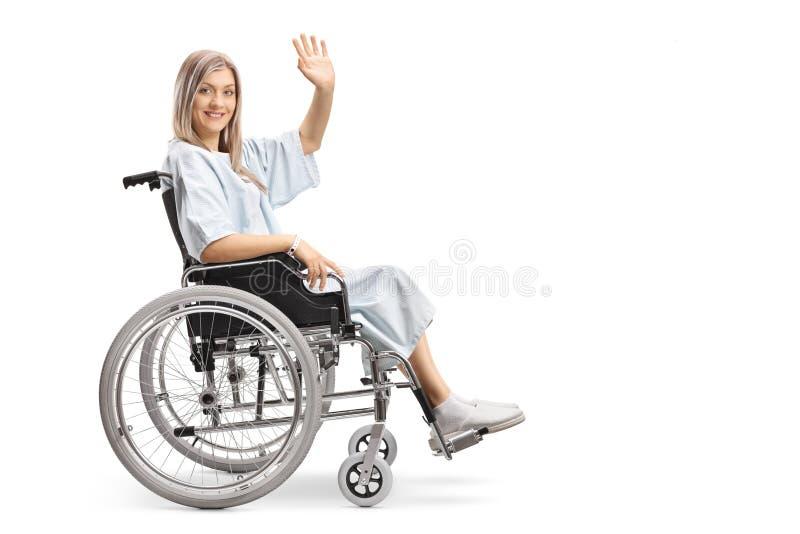 Patient féminin de sourire dans un fauteuil roulant ondulant à la caméra images stock