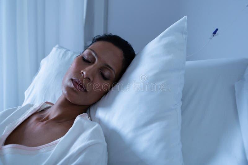 Patient féminin dormant sur le lit image stock