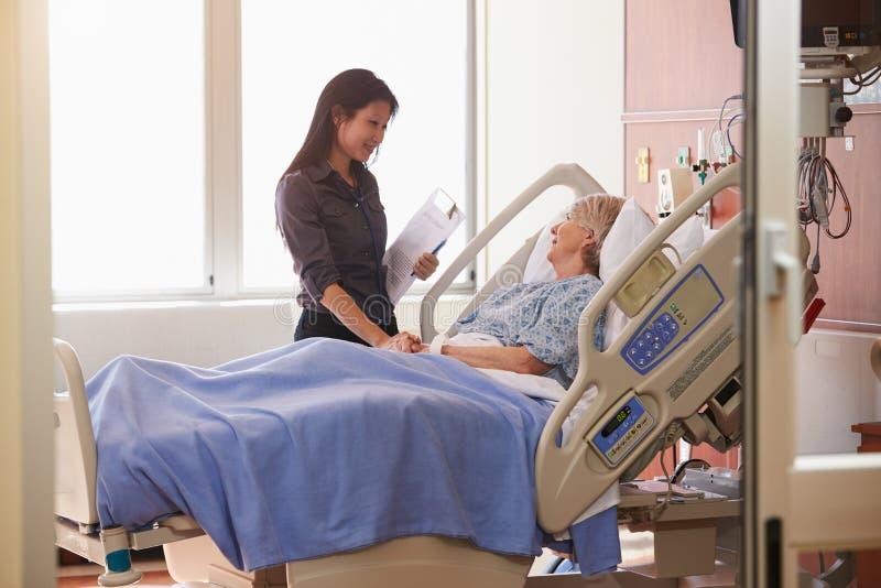 Patient féminin féminin de docteur Talks To Senior dans le lit d'hôpital photos libres de droits