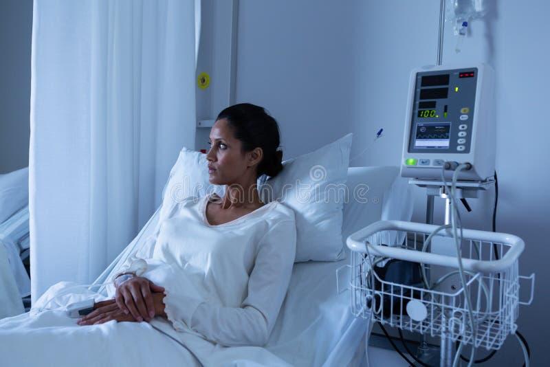 Patient féminin regardant loin tout en détendant sur le lit de l'hôpital photographie stock libre de droits