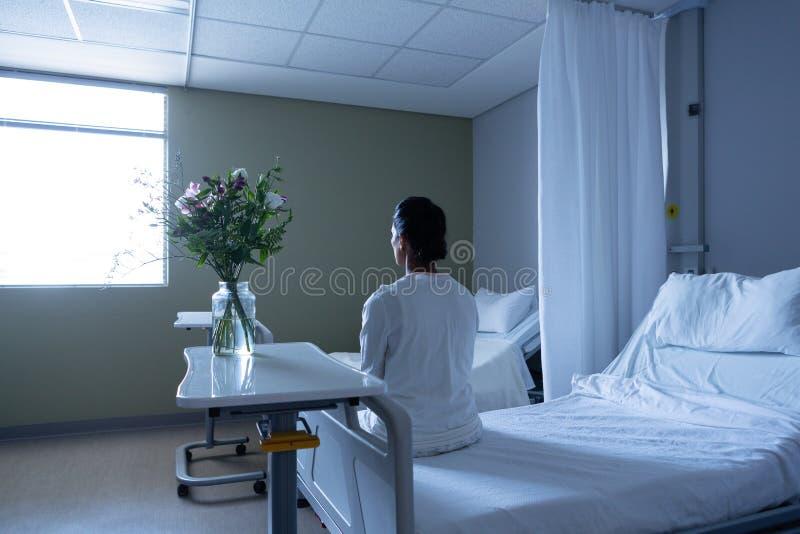 Patient féminin regardant loin tout en se reposant sur le lit image libre de droits
