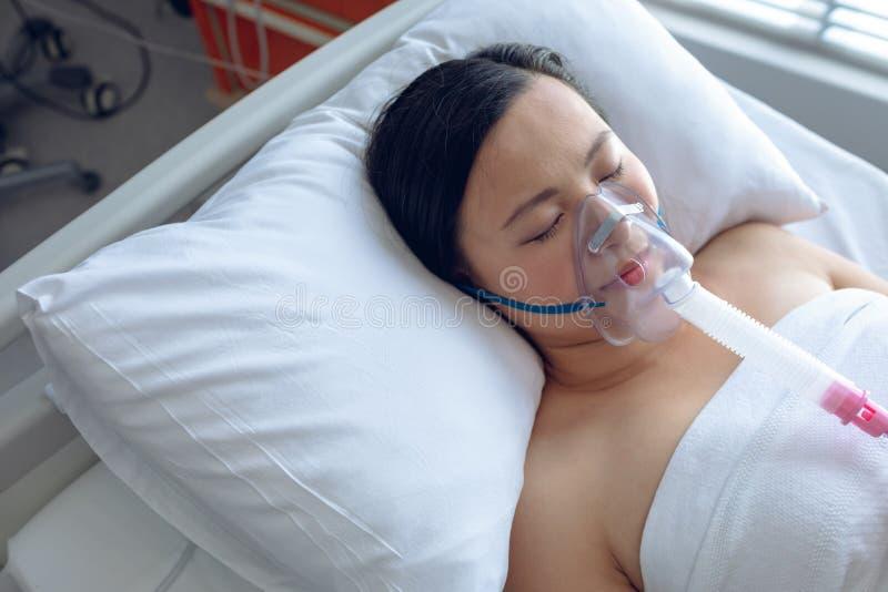 Patient féminin se reposant sur le lit dans la salle à l'hôpital image stock