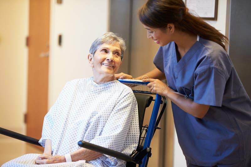 Patient féminin supérieur étant enfoncé le fauteuil roulant par l'infirmière image stock