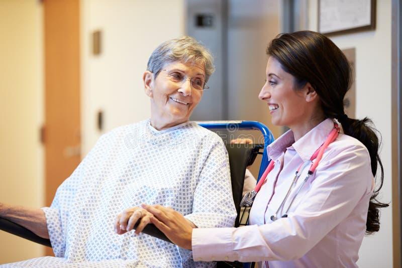 Patient féminin supérieur étant enfoncé le fauteuil roulant par le docteur images stock