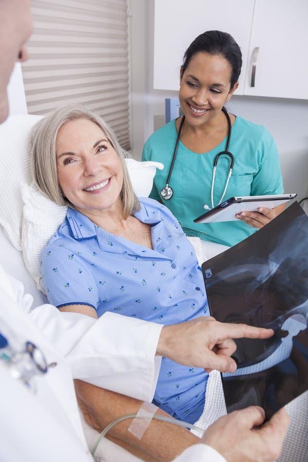 Patient féminin supérieur avec le docteur de rayon X, d'infirmière et de mâle photos stock