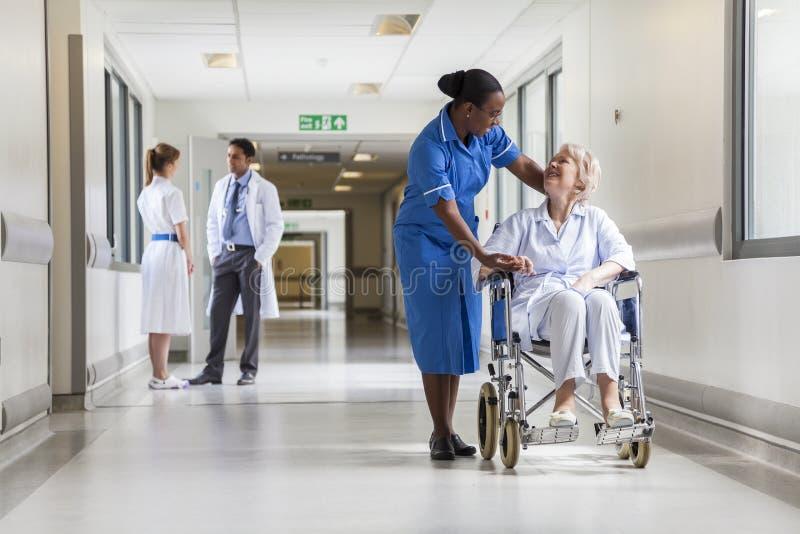 Patient féminin supérieur dans le fauteuil roulant et l'infirmière dans l'hôpital images stock