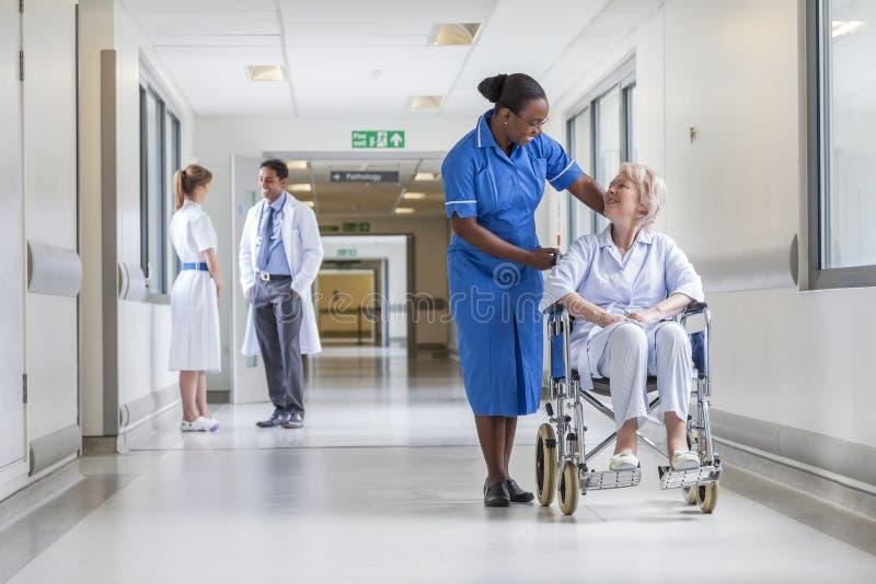 Patient féminin supérieur dans le fauteuil roulant et l'infirmière dans l'hôpital photographie stock libre de droits