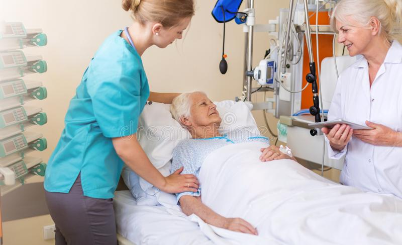 Patient féminin supérieur dans le lit d'hôpital images stock
