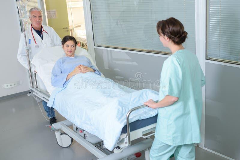 Patient féminin sur la civière ou le chariot d'hôpital étant enfoncé l'hôpital photos stock