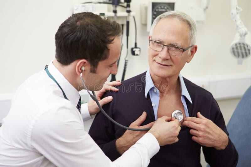 Patient för doktor Examining Senior Male i sjukhus royaltyfri fotografi