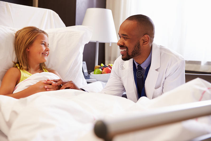 Patient för doktor Talking To Child i sjukhussäng arkivfoto
