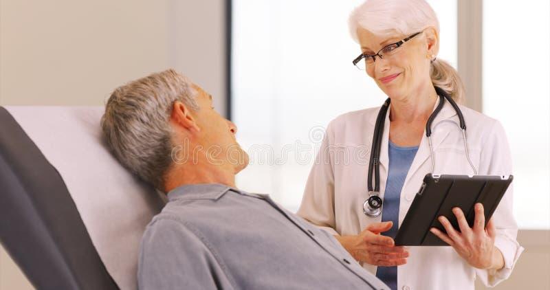 Patient för hög man som talar med doktorn om hans vård- bekymmer arkivbild