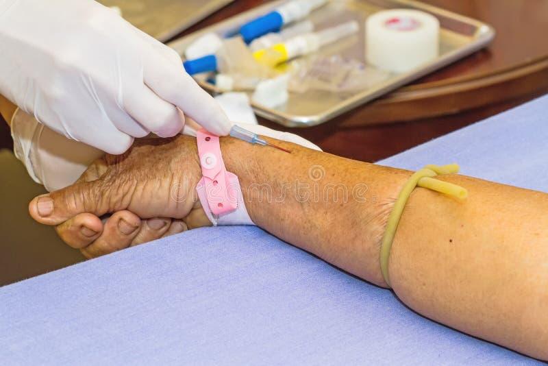 Patient för intravenös vätska för sjuksköterska en öppen för injektion royaltyfri fotografi