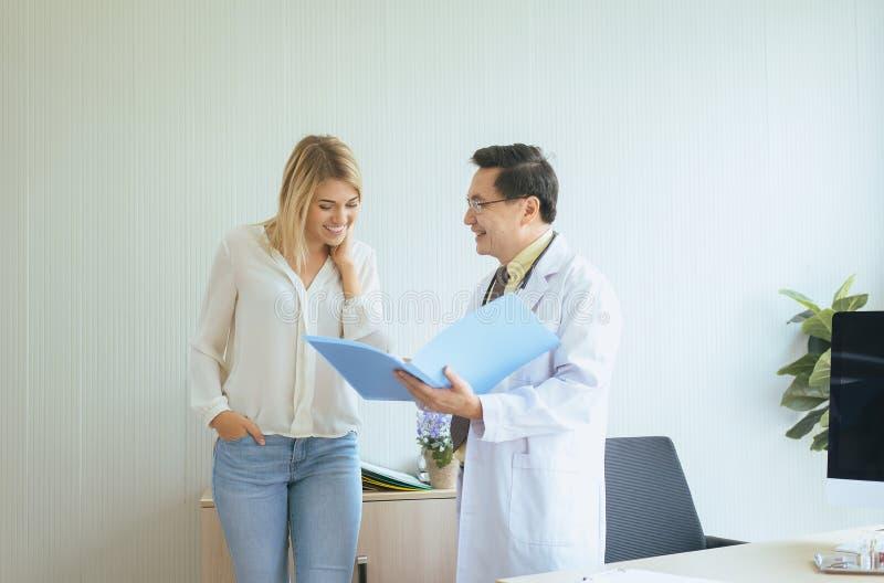 Patient för kvinna för mandoktor undersökande och att följa upp behandling på sjukhuset och lyckligt och le folk fotografering för bildbyråer