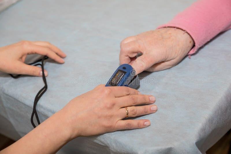 Patient för syre för doktorsmåttblod på sängen med oximeteren Medicinsk utrustning Doktor som använder pulsoximeteravkännaren på royaltyfria bilder