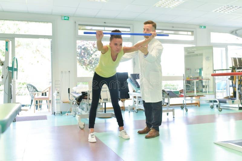 Patient för ung kvinna som gör fysiska övningar i rehabiliteringstudie royaltyfri fotografi