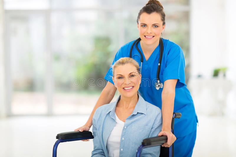 Patient female nurse. Pretty mid age patient with friendly female nurse royalty free stock image