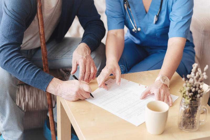 Scaled up view on nurse assisting patient at signing documents royalty free stock image