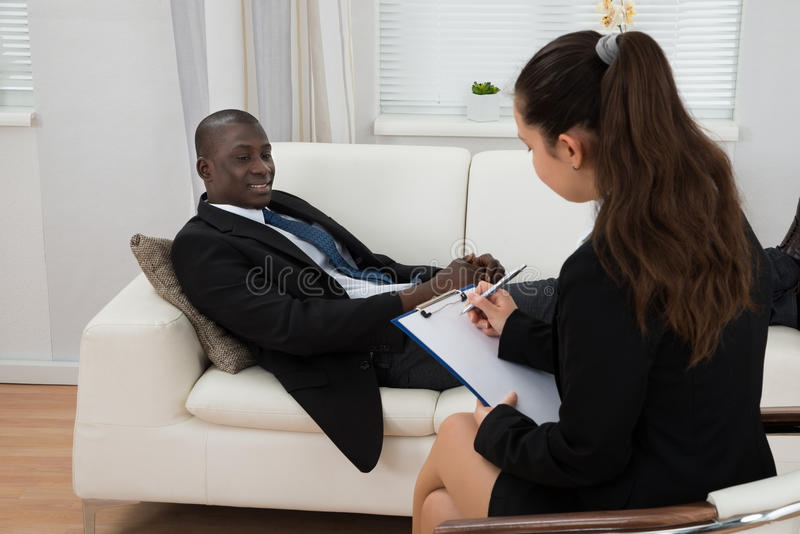 Patient In Front Of Psychiatrist Taking Notes. Young African Patient On Couch In Front Of Female Psychiatrist Taking Notes stock photos