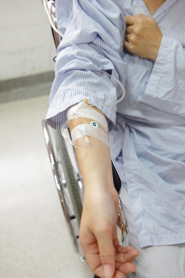 Patient hand with an intravenous drip stock images