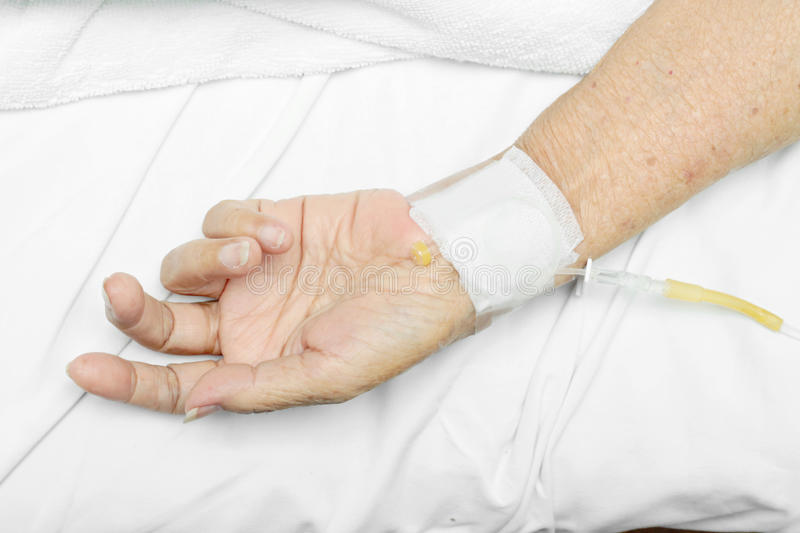Patient hand with an intravenous drip royalty free stock image