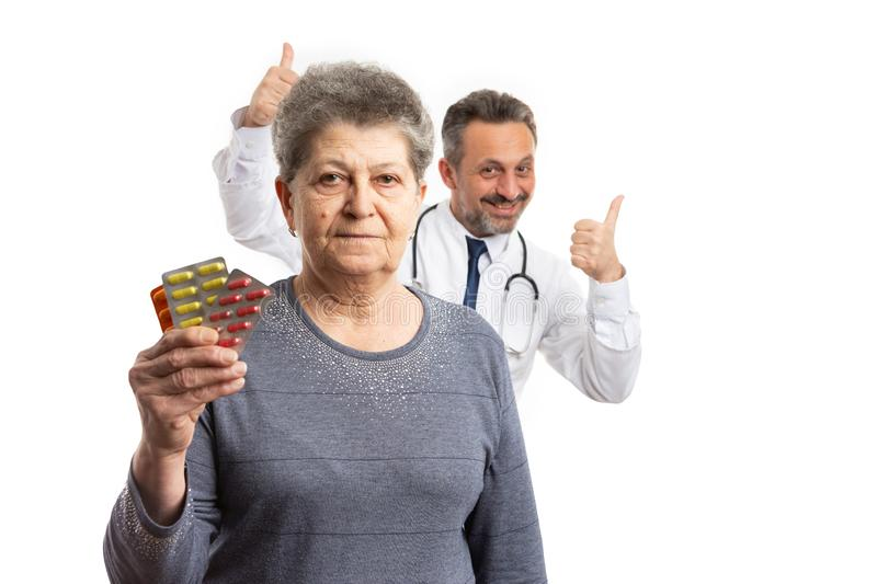 Patient holding medicine and medic holding thumbs up behind stock photos