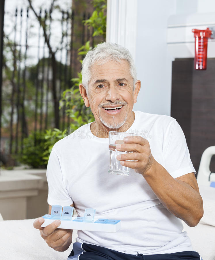 Free Patient Holding Pill Organizer And Water Glass In Rehab Center Stock Photos - 72985263