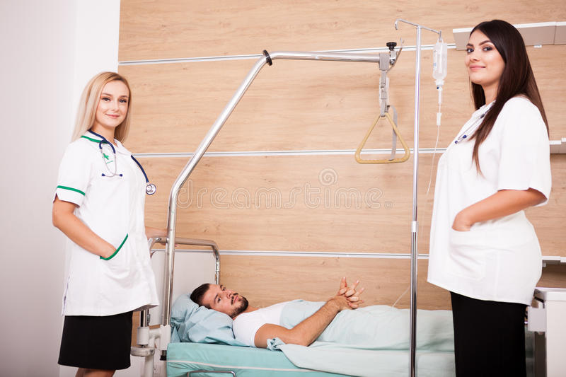 Patient in hospital room next to nurses royalty free stock images