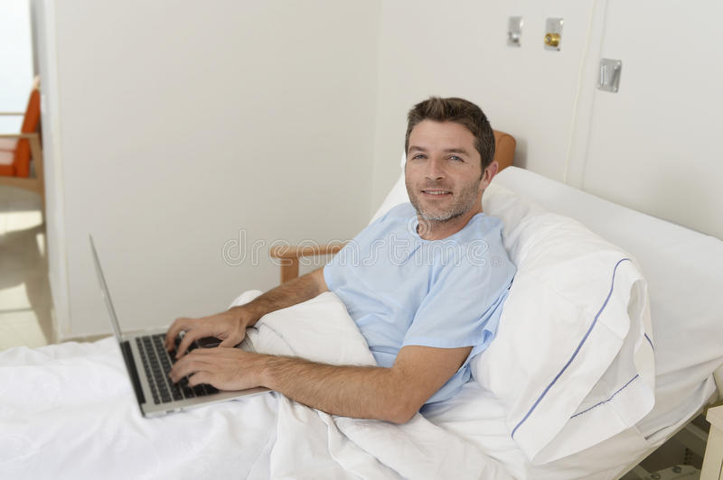 Patient in hospital suffering disease and working at the clinic bed with laptop computer smiling happy. Young businessman intern as patient in hospital suffering stock image